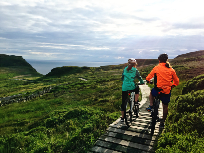 Image of two people riding there bicycles and enjoying the scenic beauty of the Isle of Man