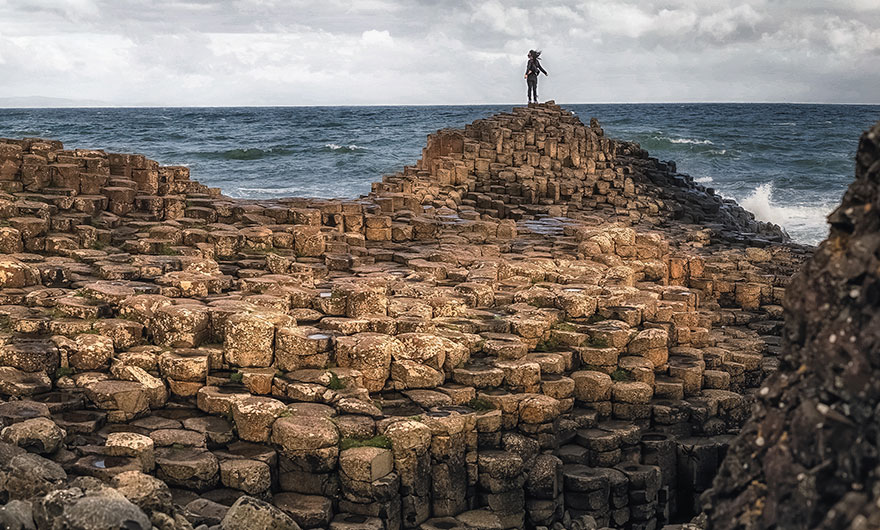 This image shows a person stood on top of the Giant's Causeway embracing the sea air.