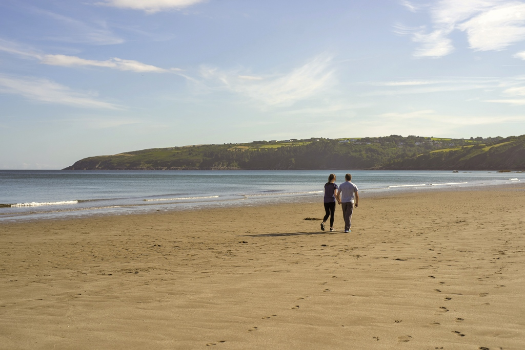 This image is of a couple enjoying a walk in the sunshine along Laxey beach Isle of Man.