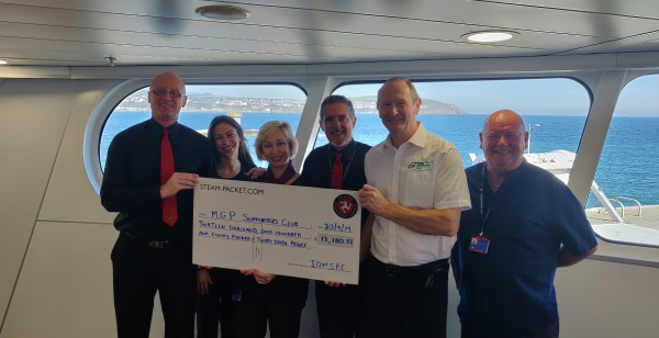 Allan Brew, MGP Supporters Club chairman, receives the cheque from IOMSPC crew members
