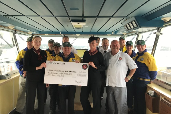 Isle of Man Steam Packet Company crew presenting Dr. David B. Stevens MBE, Director of the Rob Vine Fund and Hogg Motorsport crew with £22,011.53 on board Ben-my-Chree