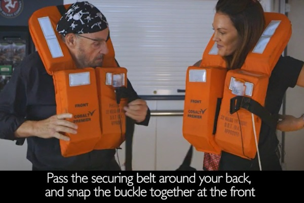 John Rhys-Davies and Karli Seed demonstrate how to put on a life jacket in the new safety video