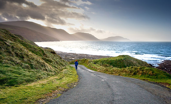 A person walking towards the scenic beauty of Niarbyl bay Isle of Man