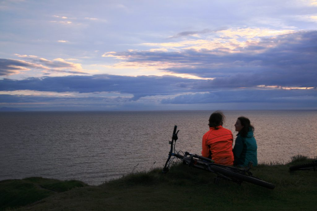 A couple sat on the coastline looking out to sea with their pedal bikes lay next to them