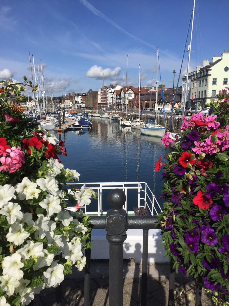 Colorful flowers overlooking the boats from Douglas Quay on a summers day.