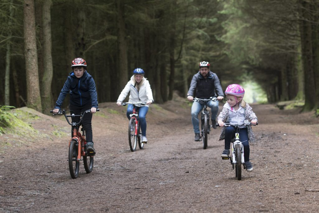 A family of four cycling through a plantation on the Isle of Man