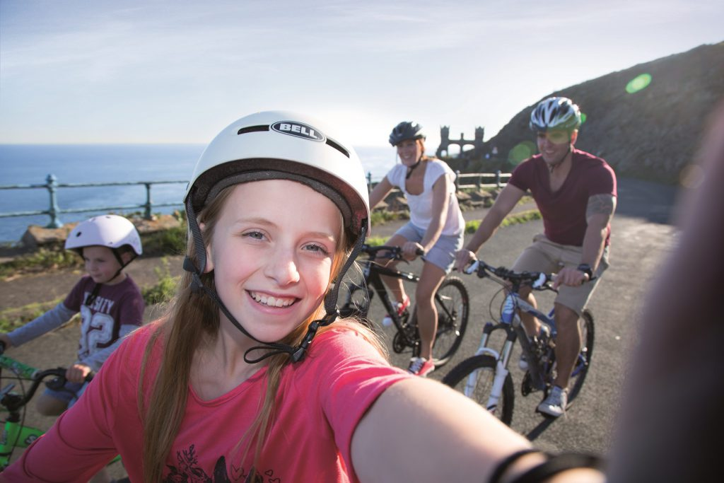 A family of four cycling on Douglas Head smiling at the camera