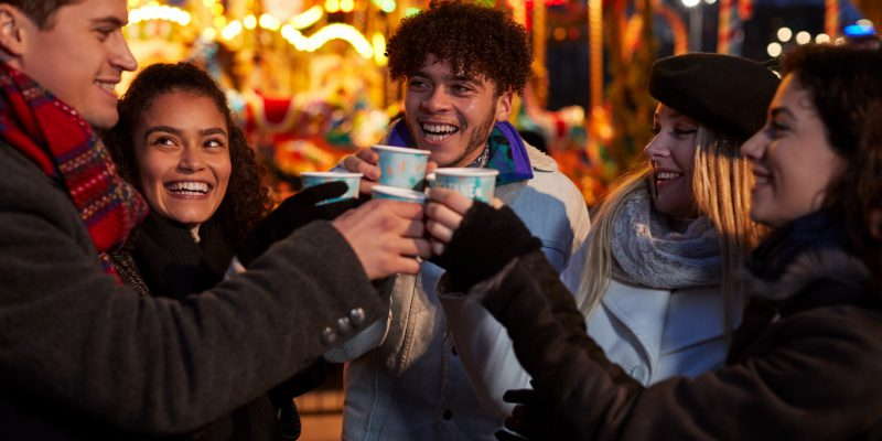A group of friends enjoying a warm festive drink at a Christmas market