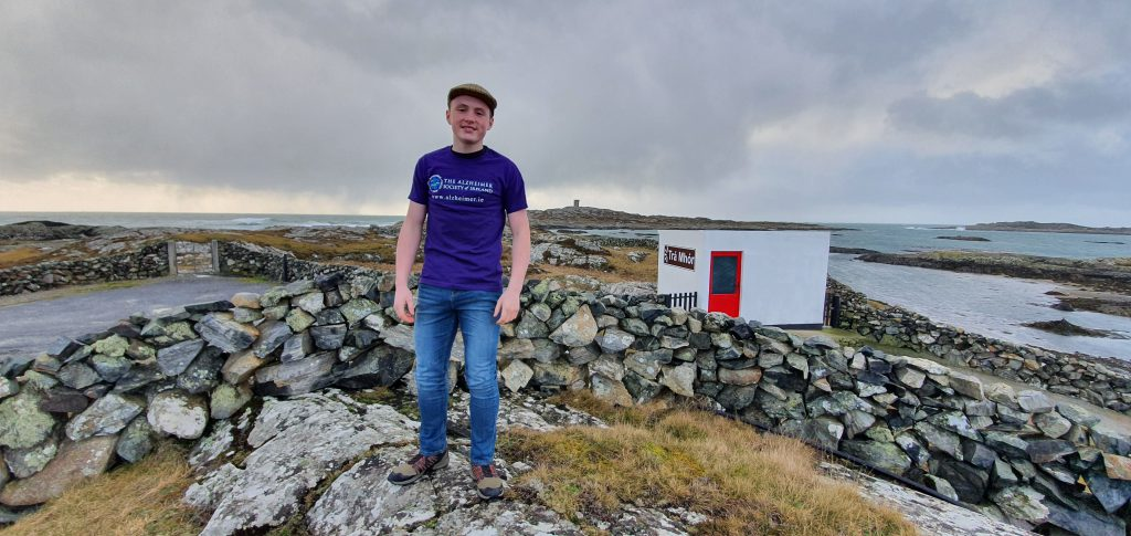 Jake Hodgson smiling and posing next to the sea in purple shirt and jeans