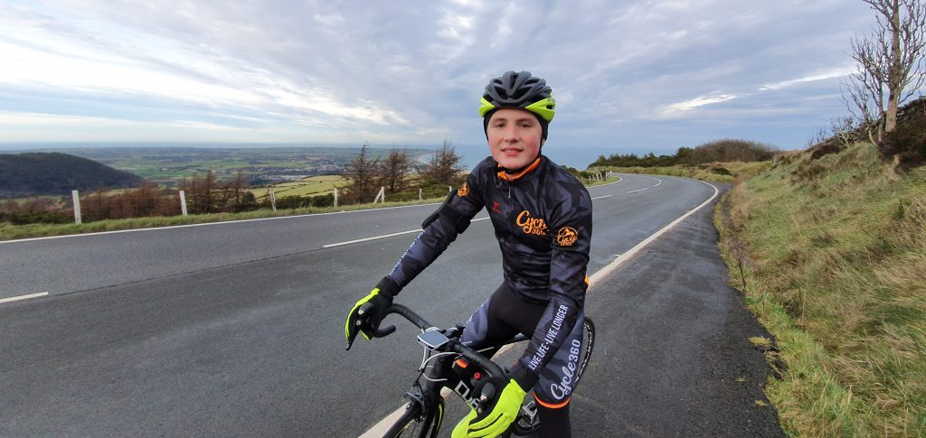 Jake Hodgson posing on his pedal bike with full cycling outfit and helmet on Isle of Man road.