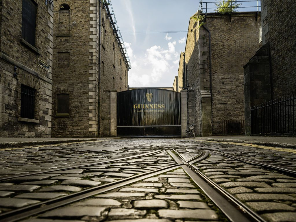 The doors of the Guinness Storehouse in Dublin with the cobbled streets in view.