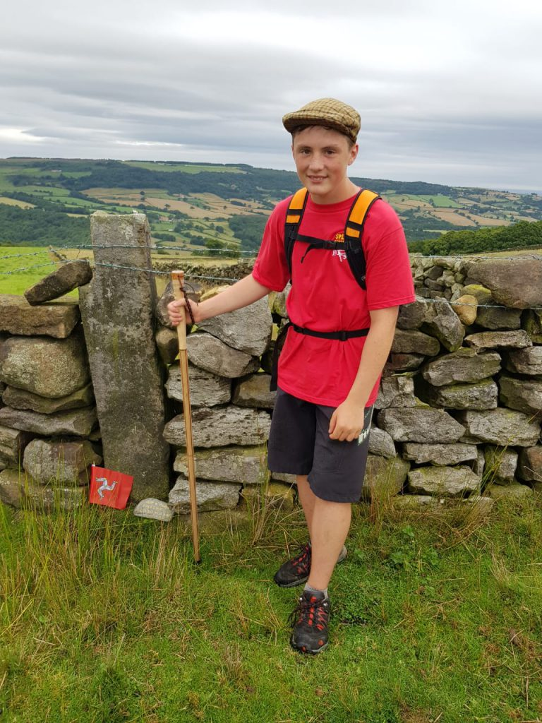Jake Hodgson stood with a walking stick in Manx countryside