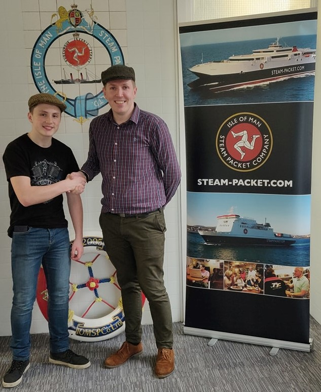 Jake Hodgson shaking hands with Steam Packet Company Business Development Executive Richard Hird next to Steam Packet Company pull up banner.