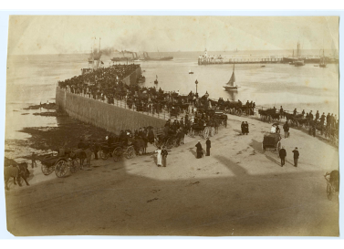 An old photo of Victoria Pier in Douglas with crowds of people milling around and a couple of boats in the background