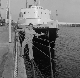 A black and white photo of Norman Wisdom posing happily next to Steam Packet Company vessel Manx Maid in Douglas Harbour