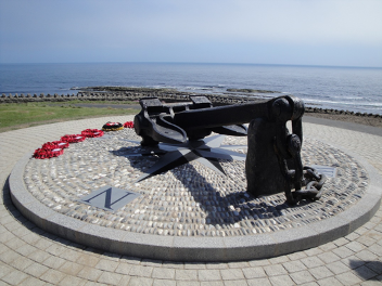 The memorial anchor of Mona's Queen at Kallow Point in Port St Mary on a sunny day, with red wreaths lay on the ground