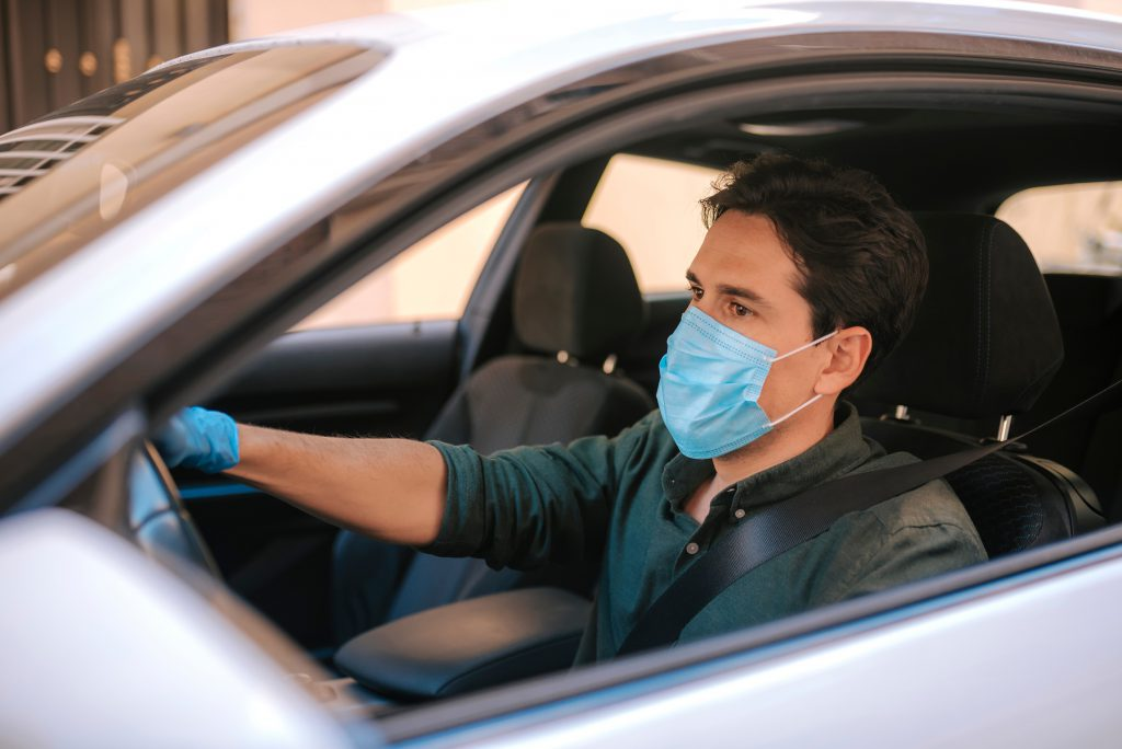 A man driving his silver car with the window down wearing a face mask