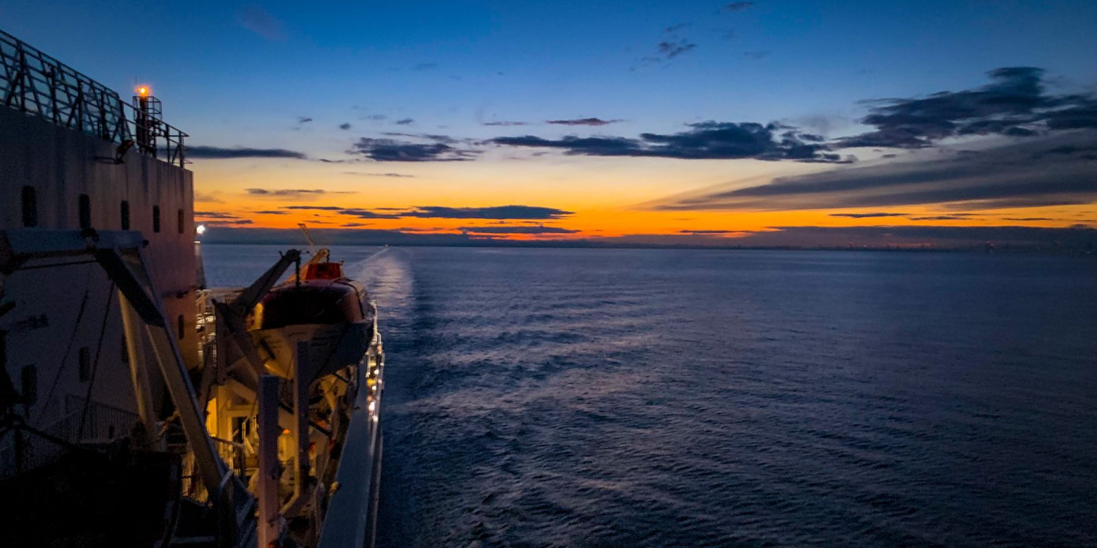 Photo taken from the side of Steam Packet Company vessel Ben-my-Chree which looks out onto blue and orange sky