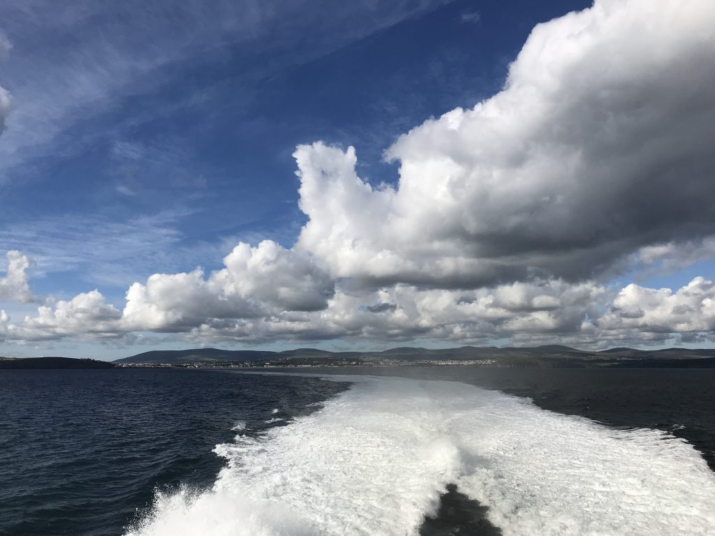 View of the blue sea, sky and clouds from the back of the vessel with the Isle of Man's coast in the distance