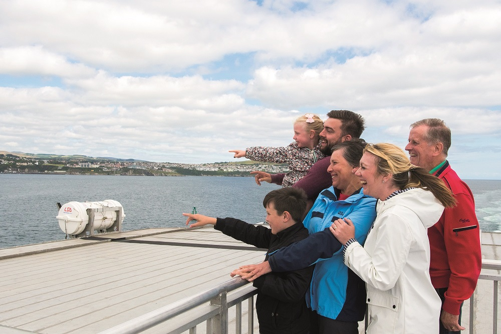 A family of six on the Steam Packet Company's Ben-my-Chree outdoor deck pointing towards the sea in the distance and smiling