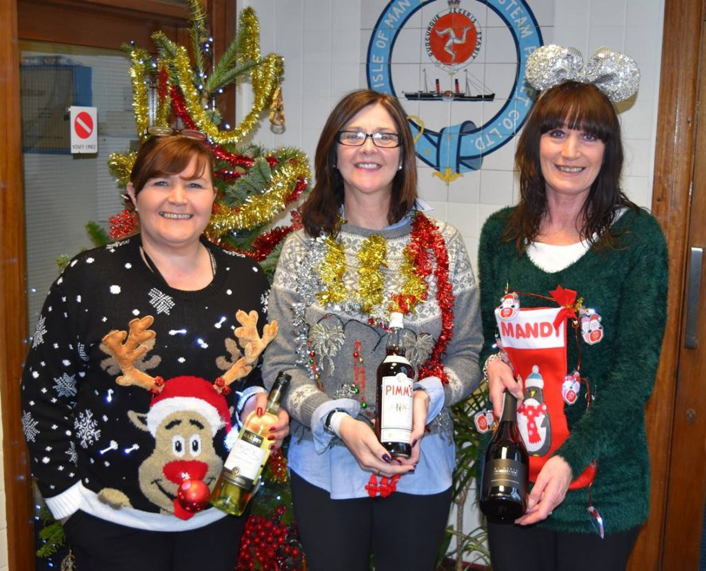 Isle of Man Steam Packet Company staff. Ethel Docherty (middle) with colleagues Vicki Winn (left) and Amanda Humphrey (right) in Christmas Jumpers with tinsel and Rudolph and bright colours on the jumpers.