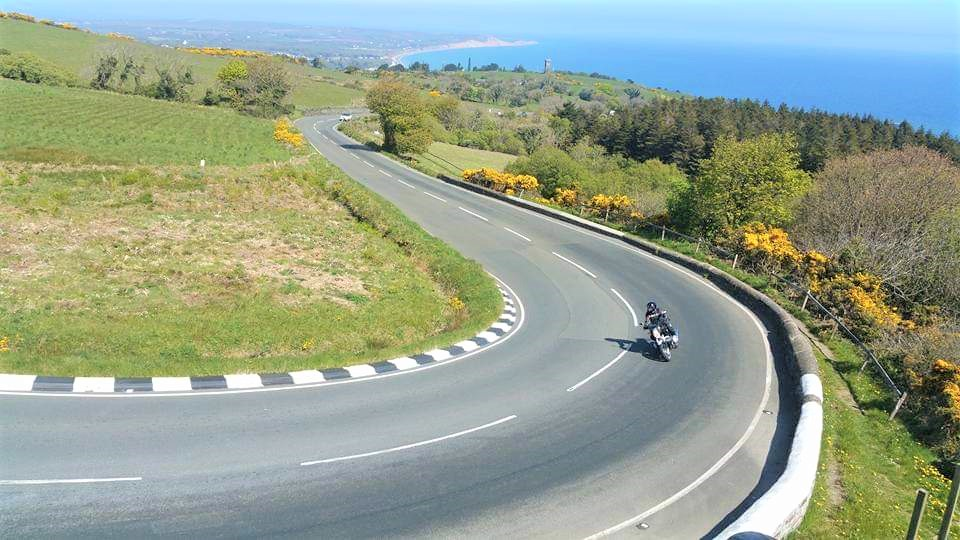 A motorbike riding on the Isle of Man's Mountain Road with Ramsey in the distance on a sunny day