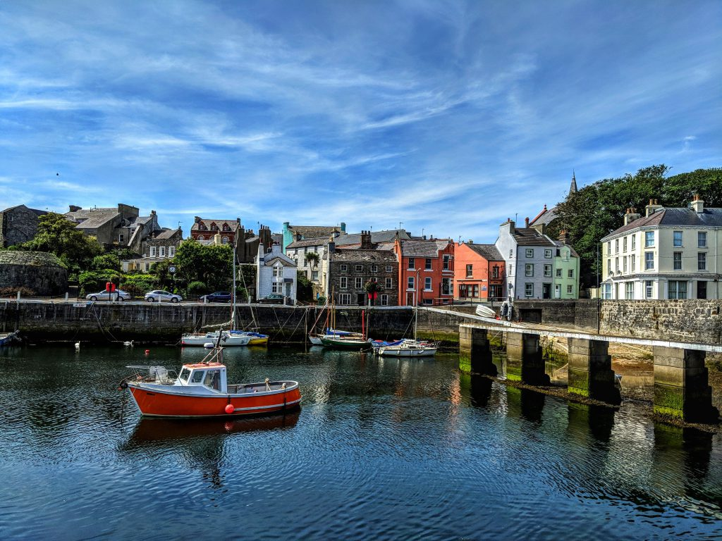 Boats sitting in Castletown Harbour on a sunny day with colourful houses in the background