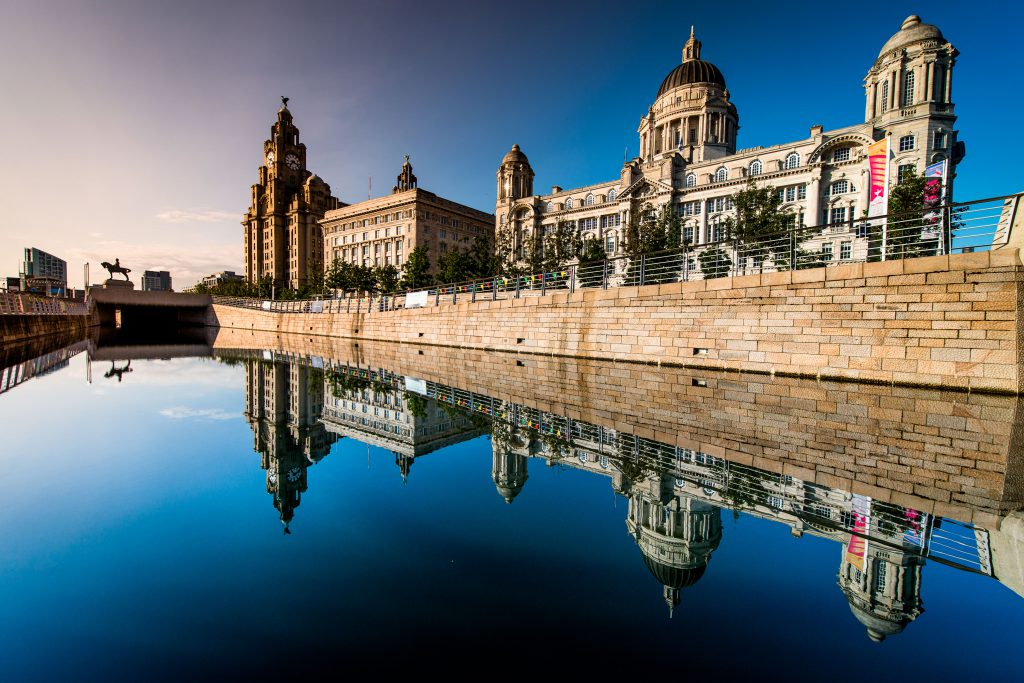 The Three Graces of Liverpool at Pier Head, with the blue sky reflecting off the water.