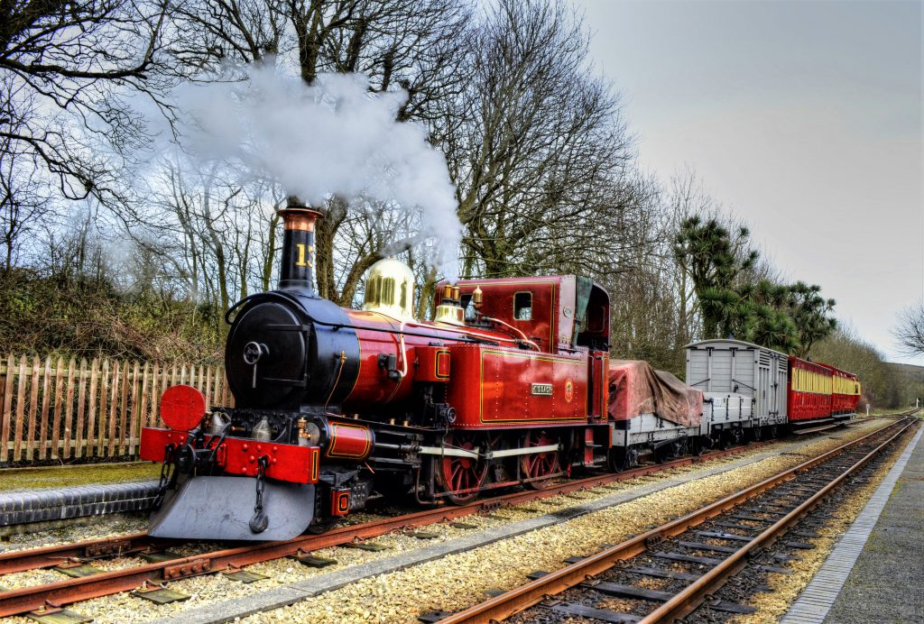 A red steam train with steam coming out - part of the Isle of Man Steam Railway
