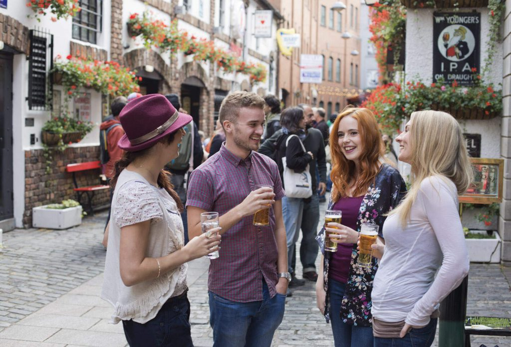A group of four young people enjoying a drink outside a bar in Belfast