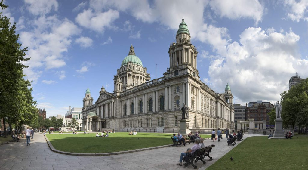 Belfast City Hall on a sunny day with people milling about outside