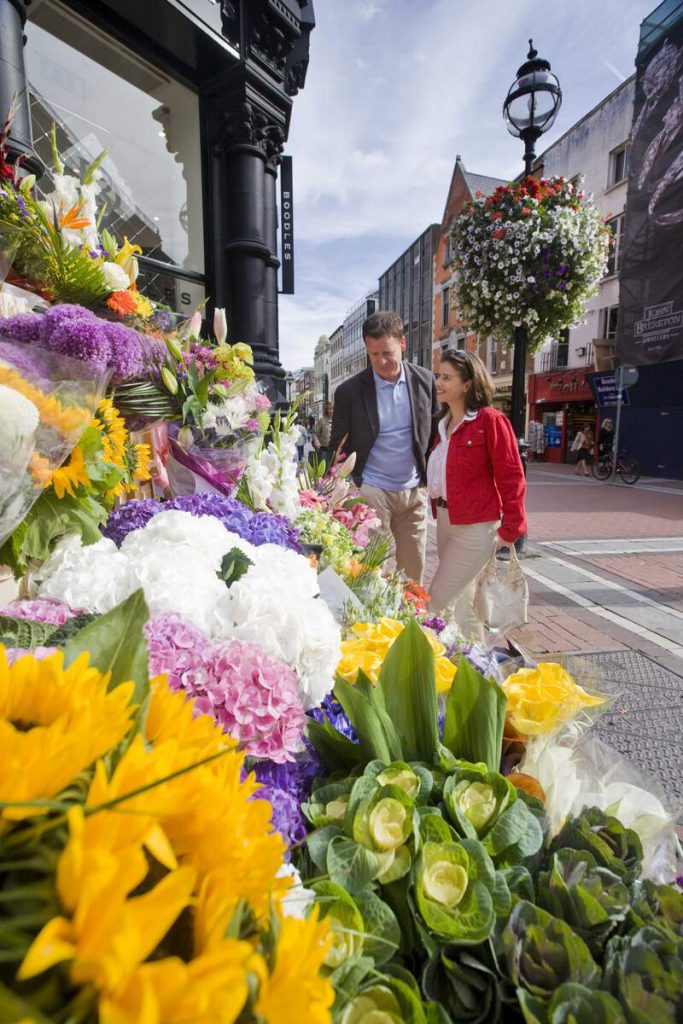 A male and female browsing a shop window in Dublin with flowers in the foreground