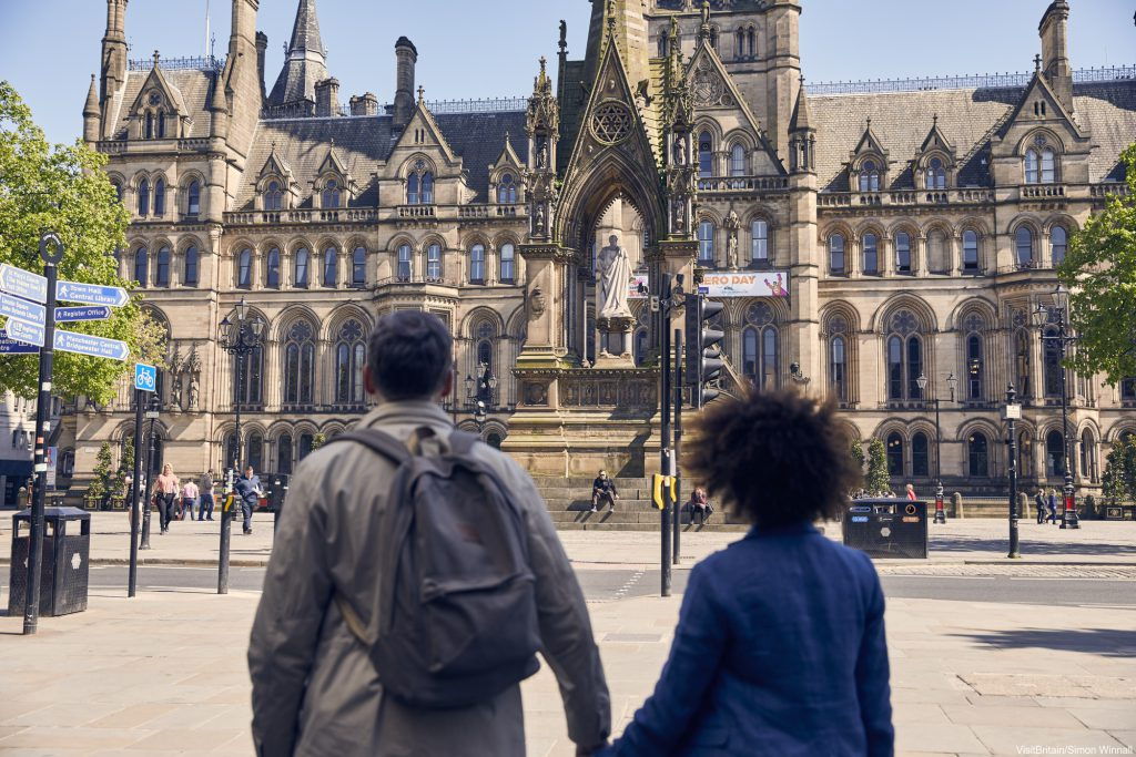 A male and female holding hands walking in Manchester city centre