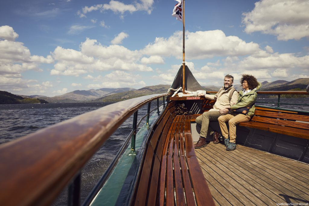 A male and female couple sat on a wooden boat in the Lake District