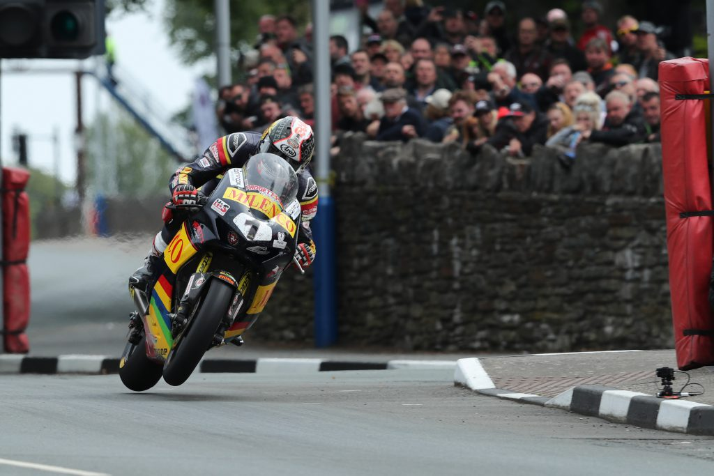 Conor Cummins on his mototbike wit a crowd in the background