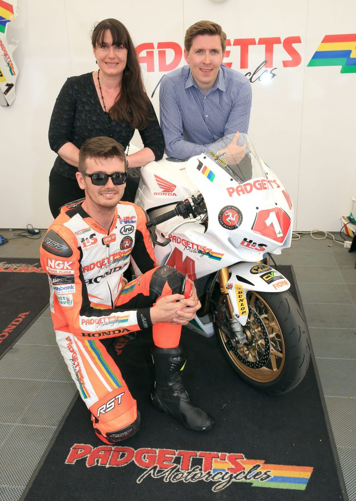 Conor Cummins in orange leathers with his bike and two members from the Isle of Man Steam Packet Company